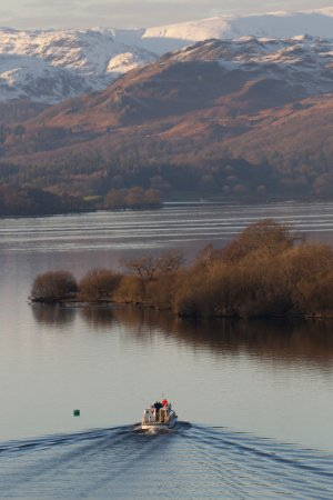 Bowness-on-Windermere, UK: Autumn colours and snow-capped Lakeland Fells, as seen from the Yellow Cruise.