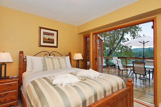 Madeira Park, Canadá: Executive Cottage bedroom with French doors to deck and private hot tub