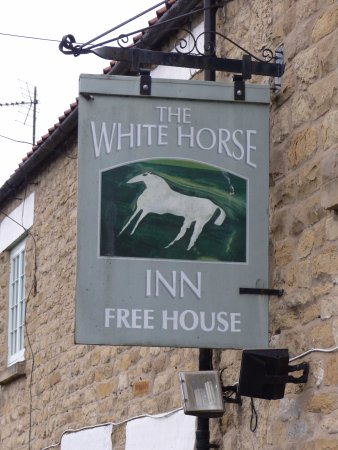 The pub sign, a tribute to the nearby White Horse near Kilburn