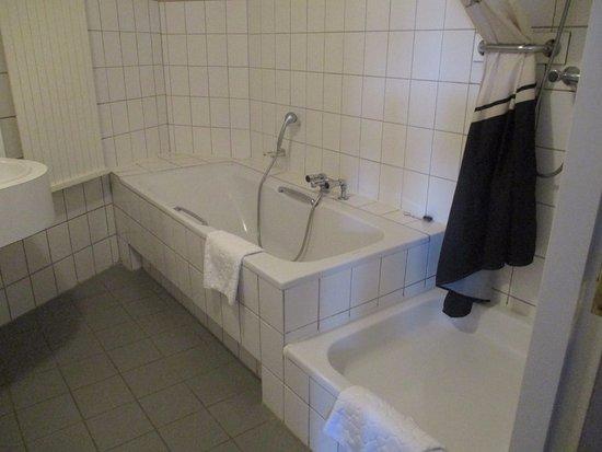 Badkamer met bad, 2 wastafels en aparte douche. - Foto van Hotel ...