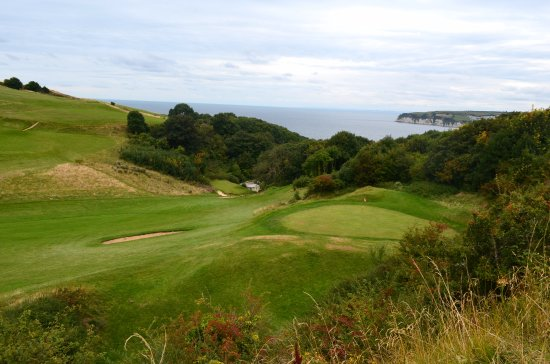 Seaton, UK: Down to the clubhouse from the 18th green. Lyme Bay in view.