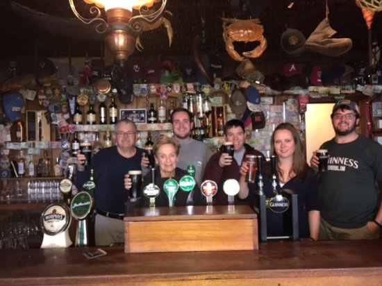 Fanore, Irlandia: The bartender insisted we all get behind the bar for our picture - Sláinte!
