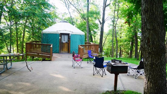 Kaiser, MO: Yurt with views of the wrap around porch and pavement area in front of the yurt.