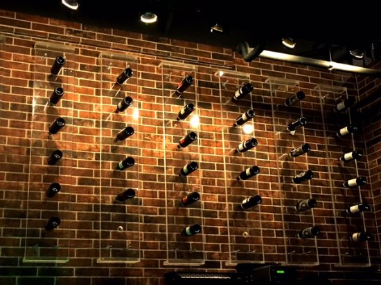 Cypress, TX: Wall-mounted wine bottle display behind bar