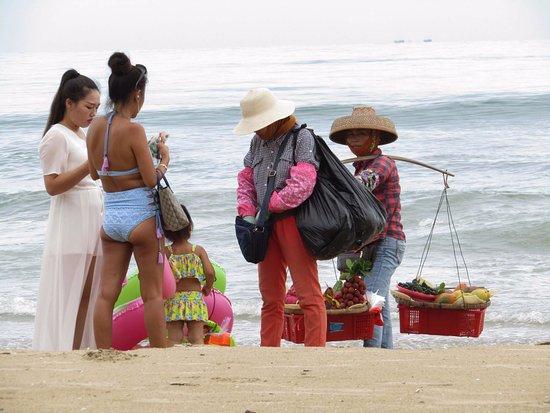 Sanya, Kina: парочки таких разных дамочек, для кого пляж - место отдыха, а для кого рабочие будни с баулами