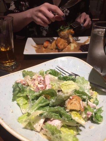 Academy Plaza Hotel: Caesar salad front, chicken in white wine sauce behind.