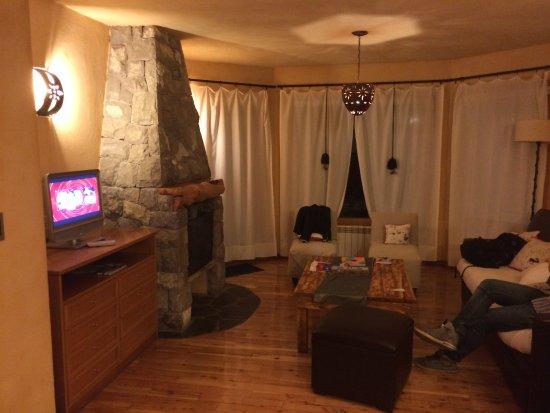 """Lirolay Suites: Sala da suíte (é integrada à """"cozinha""""), com lareira e um sofá-cama!"""