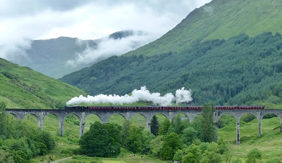 Glenfinnan, UK: The Lancashire Fusilier steam engine crosses the viaduct with a full head of steam.