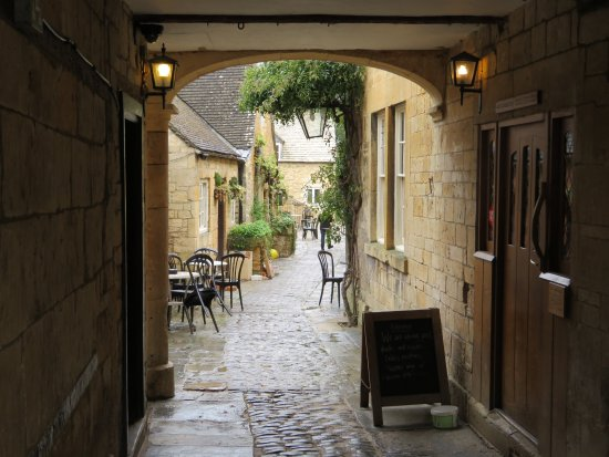 Temple Guiting, UK: an archway leading to a restaurant with outdoor seating