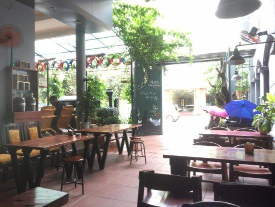bên trong quán cafe, bàn ghế gỗ, cửa cào màu xanh