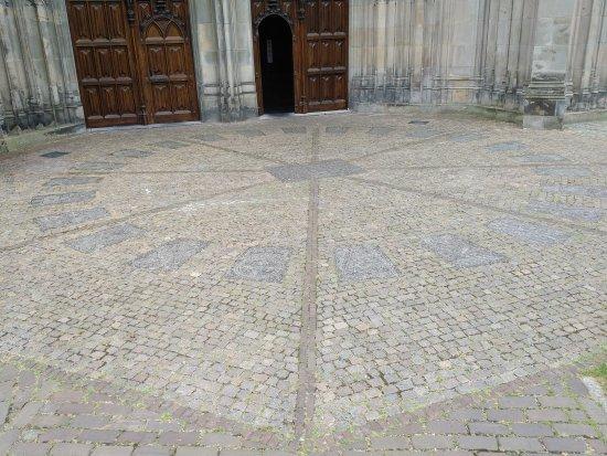 """Sint Janskathedraal (St.-Johannes-Kathedrale): Buiten de noorder ingang liggen 24 """"zerken"""" met de gildetekens. Een soort wiel of mandala."""