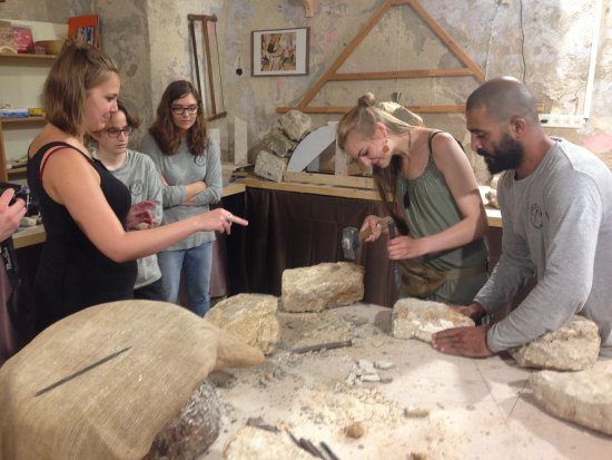 Acre, Israel: tourist enjoys the touch of the traditional stone carving tools