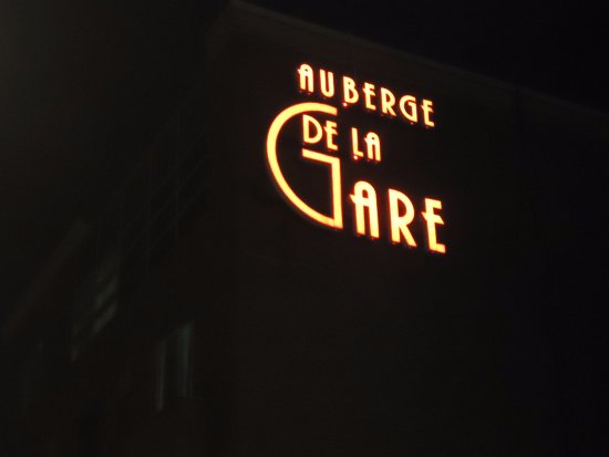 Auberge de la Gare: sign bright at night :)