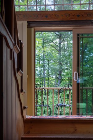 Eaton, NH: Indoor view of the Carriage House leading to the outside balcony with two chairs.