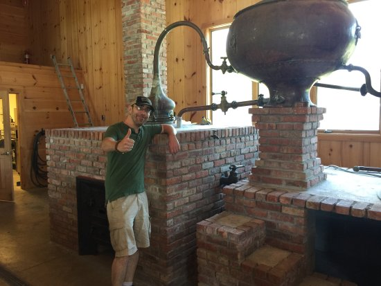 Gardiner, NY: Lyon, our wonderful tour guide, is giving thumbs up next to a 19th century French distiller, the