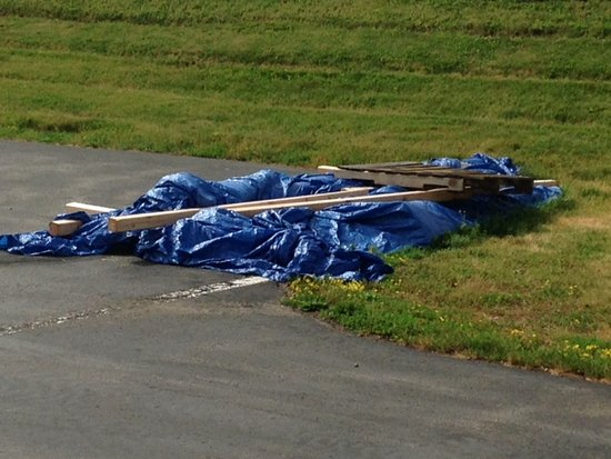 Covered tarp in parking lot left unattended. Garbage? Renovation?