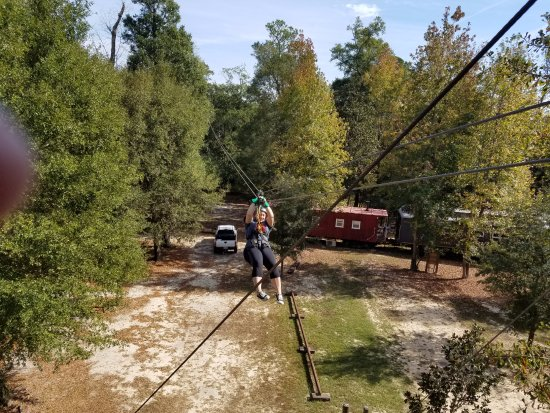 Milton, FL: Zipping over the parking area. The train cars are actually cabins for rent.