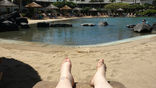 The Point at Poipu: Laying on a lounger under an umbrella by the pool.