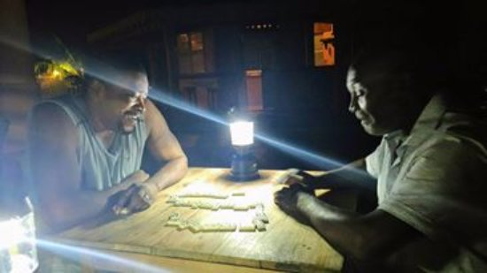 Pimento Lodge Resort: Dominoes!! the ceiling light burnt out but we just LOVED the campfire lighting instead!!