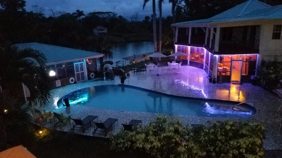 Burrell Boom, Belize: Restaurant, bar and pool area, with river in the background. Evening, in the rain. Still nice!