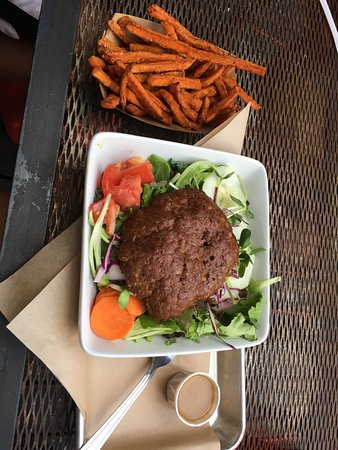 Salad with patty on top. Sweet potato fries