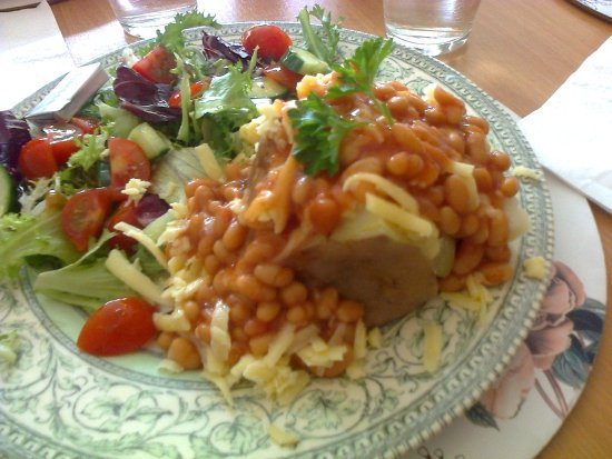 A Large Jacket Potato With Cheese Baked Beans And Salad At The