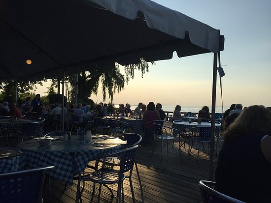 Webster, NY: Back patio by the lake. (Previous visit; umbrellas were not up at that time of day)