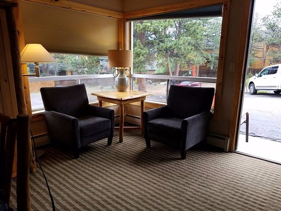 Hotel Estes : Corner area in 3 bedroom suite, double chairs looking out, dresser for clothes & holds TV.