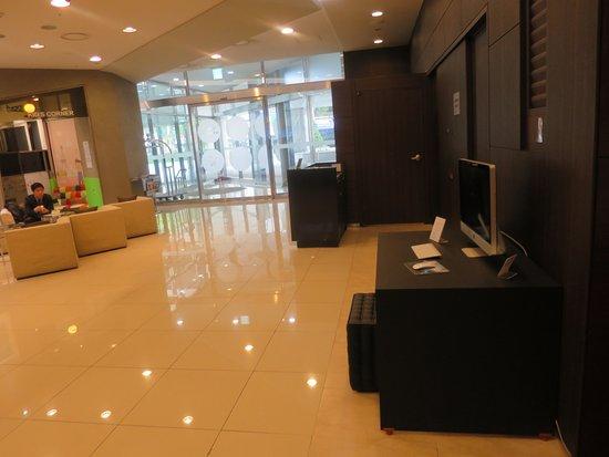 Novotel Ambassador Daegu: Hotel lobby with a computer & printer on a desk (foreground)
