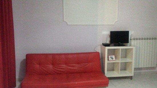 Qualiano, Italia: Il divano rosso e il mobile TV.