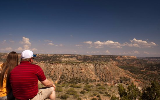 A couple sitting at the Welcome Center looking into the canyon