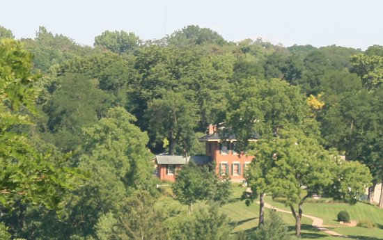 Exterior photo of the Grant Home, taken from across the Galena River on top of a hill.