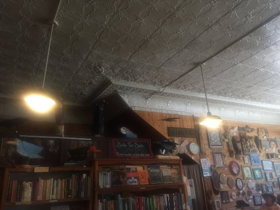 Mancos, CO: the old tin ceiling, book shelves and more art for sale on the wall.