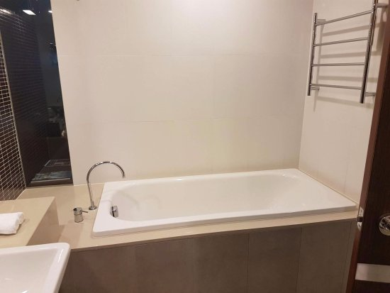 Pullman at Sydney Olympic Park: The bath as you come into the bathroom. There is a glass panel that you can see the bed through.