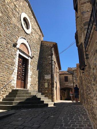 Sant'Angelo in Colle, Italia: Entrada da trattoria, panacotta e a igreja na frente.