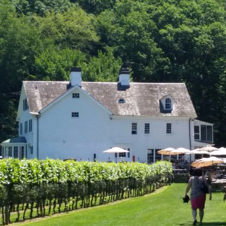 Smithtown, Estado de Nueva York: The back of the vineyard manor with tables and umbrellas set up on the rear patio.