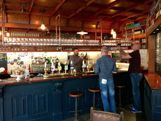 Halifax, UK: The bar with copper pipework glass shelf above.