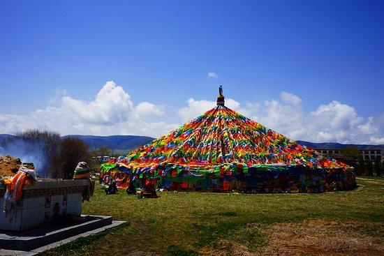 Ξινίνγκ, Κίνα: A Tibetan stupa decorated with prayer flags by the lakeside.