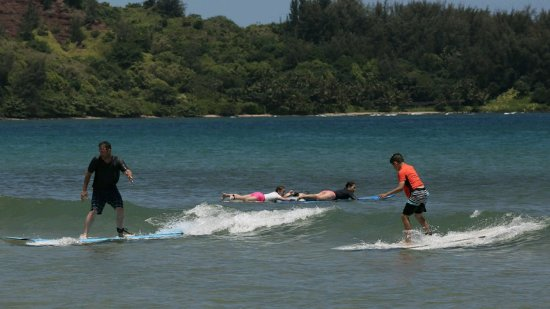 Hanalei, HI: First time, Dad and son together. Mom and the girls paddling out for to catch another wave.