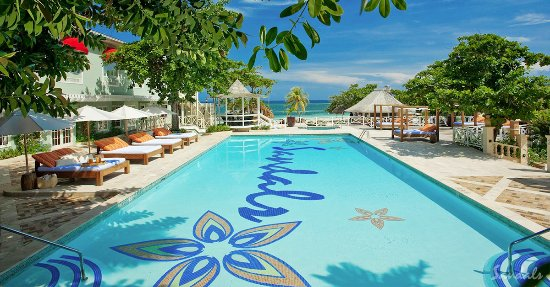 Sandals Montego Bay : Lush foliage and two-person lounge beds adorn the Main Pool.