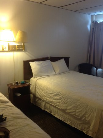 The Freeport Inn and Marina: View of bed, side table and curtain.