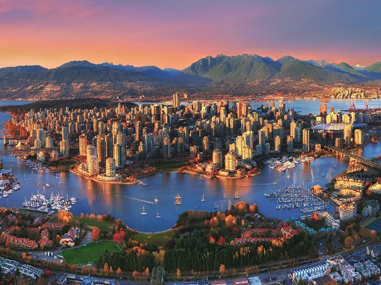 A sunset aerial capturing downtown Vancouver and the North Shore mountains