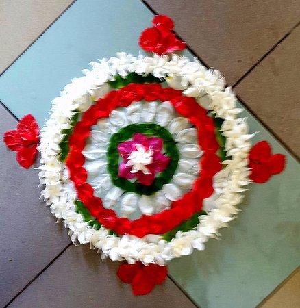 Ayurveda Paragon: Blumenmandala unter dem Behandlungstisch.