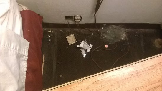 Heath, OH: Trash behind bedside table, open electric socket