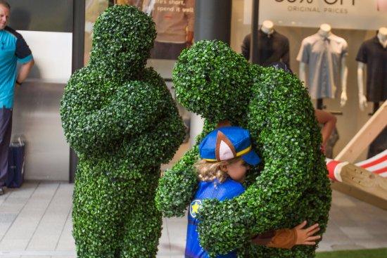 London Designer Outlet: Fun Hedge Men hugging a child guest at LDO