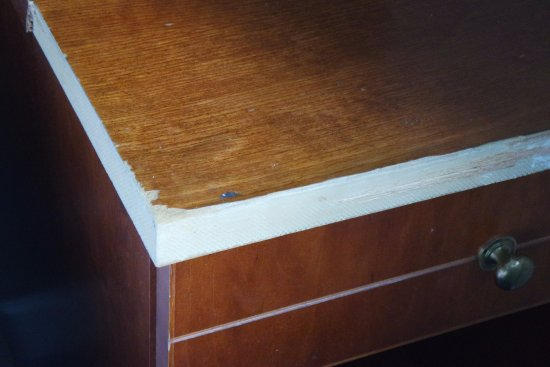 split wood with edging missing on bedside cabinet - Picture