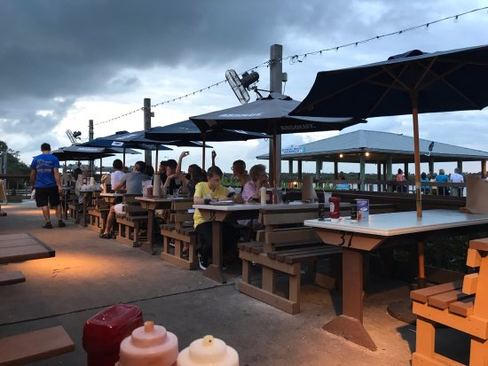 J.B.'s Fish Camp & Restaurant: Picnic style dining outdoors with a storm rolling in at J.B.s Fish Camp