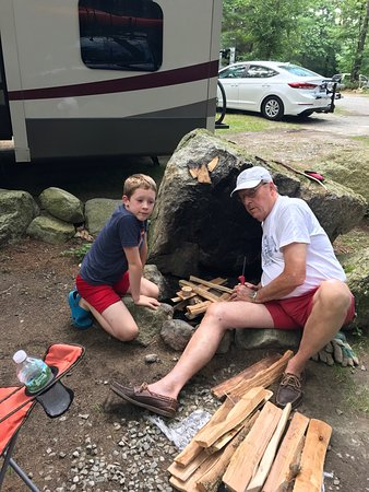 Littleton, MA: Grandpa making a fire with grandson in beautiful rock fire pit at our campsite.