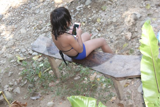 Malay, Philippines: A young girl enjoying her moment in a long wooden bench while watching tourists in the river.