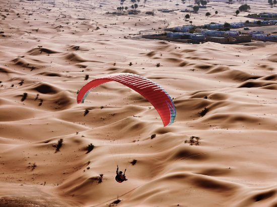 Шарджа, ОАЭ: Try paragliding for a falcon's view of the dunes of Mleiha